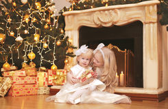 Christmas, celebration, holiday, xmas concept - happy cute child. Ren with gifts near christmas tree and fireplace Stock Photography