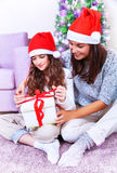 Christmas celebration at home. Pretty mother giving present to her cute daughter, happy facial expression, beautiful decorated Christmas tree, loving family Royalty Free Stock Photo