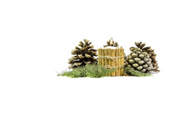 Christmas centerpiece. Closeup image of a candle surrounded by cinnamon sticks and some pine cones, over a white background Royalty Free Stock Photography