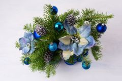 Christmas centerpiece with glitter baubles, blue silk poinsettia royalty free stock photos