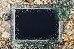 Christmas chalk board with silver frame. Golden Christmas decorations and fir branches on black matte background, New Year frame, top view, copy space Stock Photos