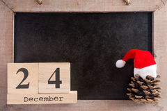 Christmas. Chalkboard with the date December twenty four and pine cone Stock Image