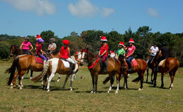Christmas charity ride. Children and their ponies, decked out in Christmas hats and tinsel, gather for a Christmas charity ride in Port Elizabeth, South Africa ( Stock Photos
