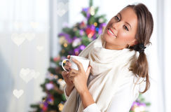 Christmas cheer. Beautiful girl with cup of warm tea in front of a christmas tree Royalty Free Stock Image
