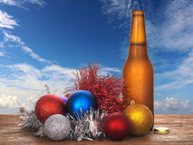 Christmas cheer - cold beer and baubles, sunshine sky. Australia maybe! Royalty Free Stock Photo
