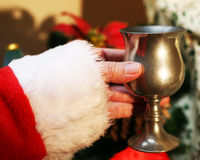 Christmas Cheer. Santa having a goblet of mulled wine, port or sherry by the  Tree Royalty Free Stock Photography