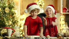 Christmas chef cook - children in Santa hat. Two children make gingerbread cookie for Santa against Christmas light
