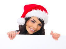Christmas chick with board. Beautiful christmas woman in santa hat holding empty board Stock Photo