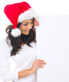 Christmas chick with board. Beautiful christmas woman in santa hat holding empty board Royalty Free Stock Images