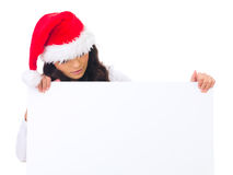 Christmas chick with board. Beautiful christmas woman in santa hat holding empty board Stock Image