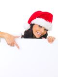 Christmas chick with board. Beautiful christmas woman in santa hat holding empty board Stock Photos