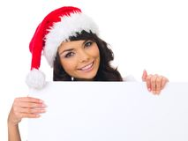 Christmas chick with board. Beautiful christmas woman in santa hat holding empty board Royalty Free Stock Image
