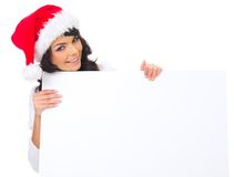 Christmas chick with board. Beautiful christmas woman in santa hat holding empty board Royalty Free Stock Photography