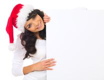 Christmas chick with board. Beautiful christmas woman in santa hat holding empty board Stock Photography