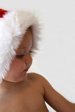 Christmas Child. Toddler with a Christmas hat looking down into the distance Royalty Free Stock Images