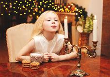 Christmas child blowing on candle makes a wish sitting at the table at home Royalty Free Stock Photography