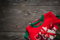 Christmas child clothes on a table. With gift and decorations. Flat lay copy space Stock Image