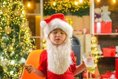 Christmas child dream. Portrait of surprised and funny Santa. Little Santa picking cookie and glass of milk at home.