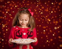 Christmas - child girl holding cookies plate on dark red with lights Royalty Free Stock Photography