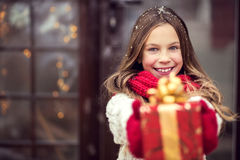 Christmas. Child giving a Christmas present near her house door, snowy outside Royalty Free Stock Images