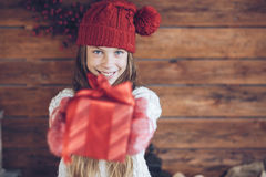 Christmas. Child giving a Christmas present on rustic wooden background, farmhouse interior Royalty Free Stock Photography