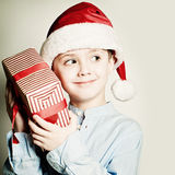 Christmas Child holdind Gift. Happy Little Boy in Santa Hat Royalty Free Stock Photography