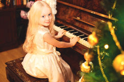 Christmas child little girl playing on piano home Stock Images