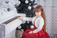 Christmas child little girl playing on piano at home Stock Photos