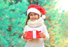 Christmas child little girl in santa red hat with gift box over branch tree Stock Image