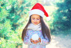 Christmas child little girl in santa red hat holding snowball near branch tree Stock Photo