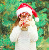 Christmas child little girl in santa red hat playing with sweet lollipop cane near  tree Royalty Free Stock Photography