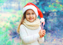 Christmas child little girl in santa red hat, sweet lollipop cane Royalty Free Stock Photos
