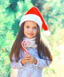 Christmas child little girl in santa red hat with sweet lollipop cane near branch tree Stock Photo
