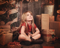 Christmas Child Making Wish in Wooden Room. A little girl is sitting on a wooden floor with Christmas decorations and presents looking up and making a wish for a royalty free stock photo