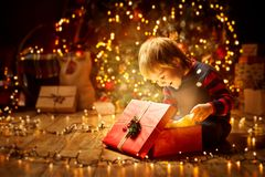 Christmas Child Open Present Gift, Happy Baby Boy looking Box stock photography