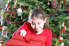 Christmas child peaking into gift Stock Image