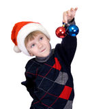 Christmas child in a red hat. Young boy with Santa Claus hat decorates a Christmas tree, isolated Stock Photo