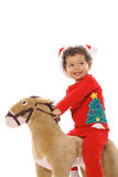 Christmas child riding a pony Royalty Free Stock Image