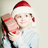 Christmas Child in Santa Hat. Happy Little Boy and Xmas Box Stock Image