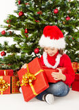 Christmas child in Santa hat, Kid open gift box present, Xmas tree Royalty Free Stock Images