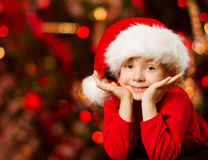 Christmas child in Santa hat smiling over red Royalty Free Stock Photos