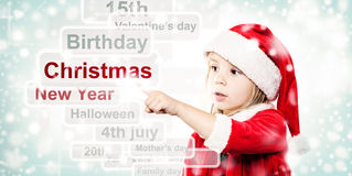 Christmas Child in Santa Hat Surfing through the Internet Stock Photography