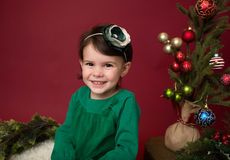Christmas Child on sled against christmas tree with ornaments Stock Photo