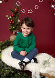 Christmas Child on sled against christmas tree with ornaments Royalty Free Stock Photography