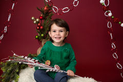 Christmas Child on sled against christmas tree with ornaments Stock Photos