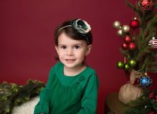 Christmas Child on sled against christmas tree with ornaments Royalty Free Stock Image