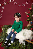Christmas Child on sled against christmas tree with ornaments Royalty Free Stock Photos