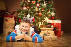 Christmas Child under Xmas Tree, Happy Boy Presents Gifts stock photo