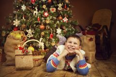 Christmas Child under Xmas Tree, Happy New Year Boy Kid royalty free stock image
