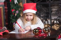 Christmas Child Write Letter to Santa Claus. Christmas Child Write Letter to Santa Claus, Kid in Santa Hat Writing Wish List stock image